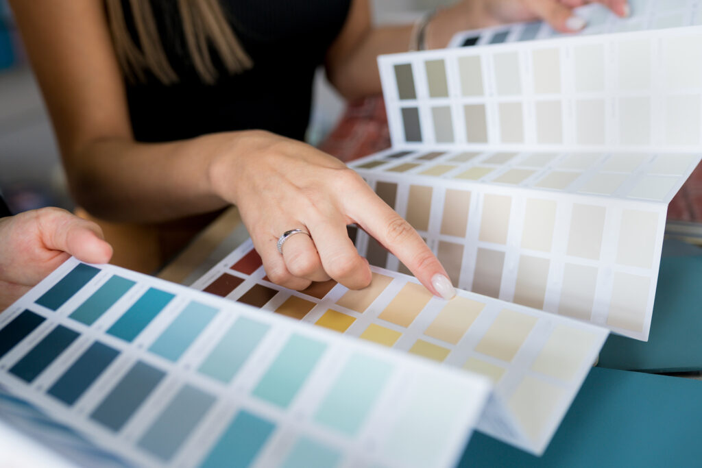 Close-up of two women choosing samples of wall paint. Interior designer consulting a client looking at a color swatch. House renovation concept